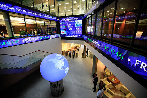 Financial data and news headlines stream accross ticker screens around the atrium of the London Stock Exchange.