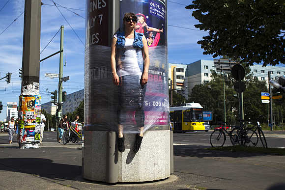 A woman is held to a rotating advertising column with cling film as a temporary installation of the Bosso Fataka street art group in Berlin.