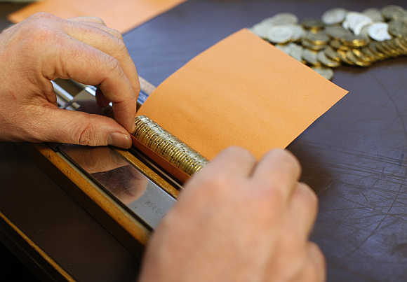 A bank employee rolls euro coins in paper in Gammesfeld, Baden-Wuerttemberg, Germany.
