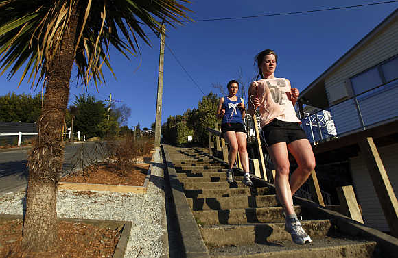 Women run down Baldwin street in Dunedin. Baldwin street is considered as one of the world's steepest streets.