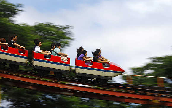 People ride on a roller coaster ride in Yangon Zoo playground in Burma.