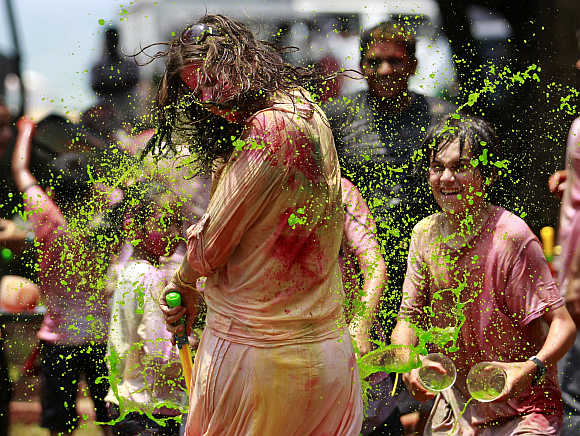 A boy splashes coloured water on a girl in Colombo.