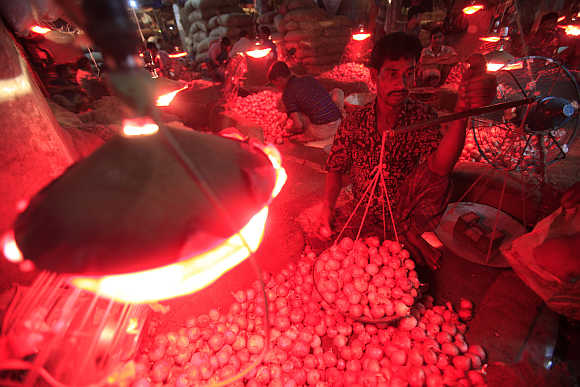 A worker weighs onions in a wholesale market at Kawranbazar in Dhaka.