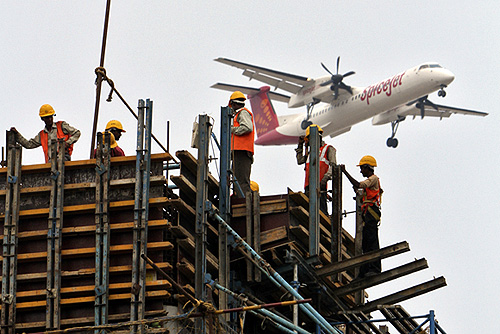 Construction workers erect scaffolding at the site of metro station as a SpiceJet Airlines aircraft flies past in Chennai.