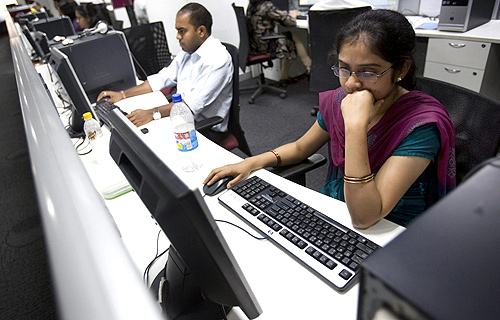 Employees work on their computer terminals on the floor of an outsourcing centre in Bengaluru.