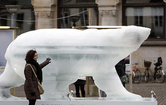 A woman touches an ice sculpture of a polar bear in downtown Copenhagen.