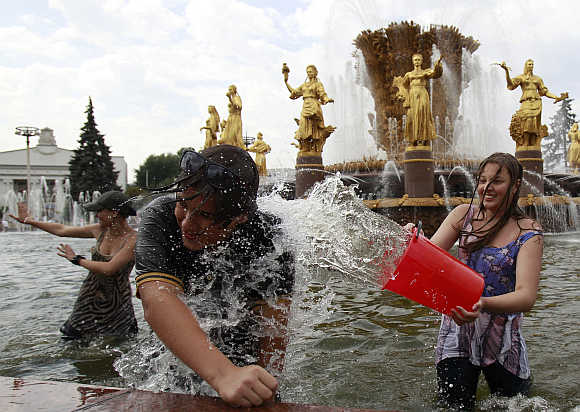 People enjoy themselves in a fountain at a public park in Moscow.