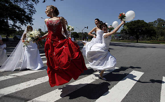 Women in wedding gowns jump on the street during a 'Parade of Brides' in Sao Paulo.