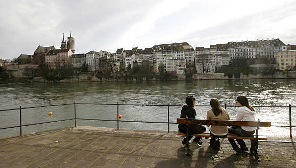 Girls sit on a bench on the banks of the Rhine River, in front of the old town of the northern Swiss city of Basel.