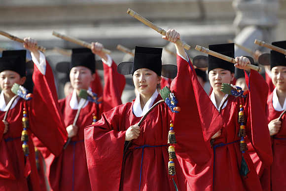 Performers in traditional Korean costumes dance during a welcoming ceremony for the Oegyujanggak books at Gyeongbok Palace in Seoul.