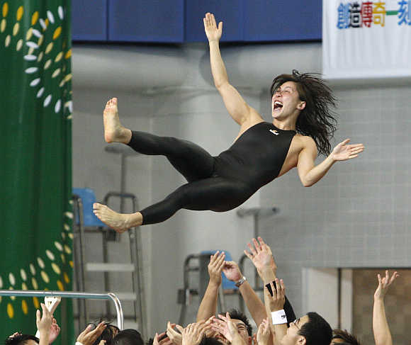 A woman is tossed into the air by teammates in Hong Kong.