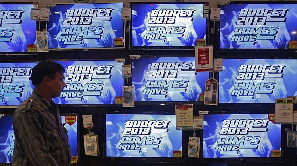 A man walks past television screens showing an advertisement for a programme on India's annual budget at an electronics shop i