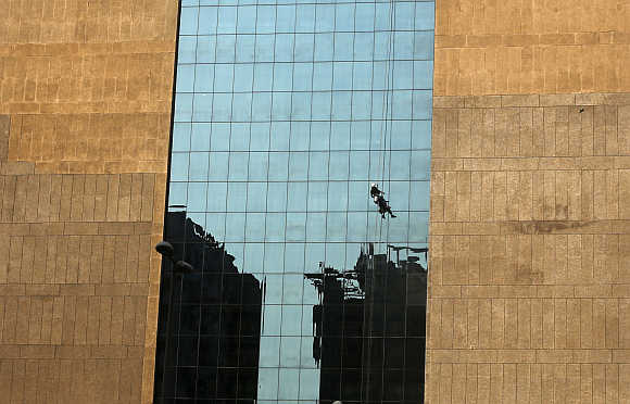A worker cleans the glass exterior of a building in the commercial hub of New Delhi.