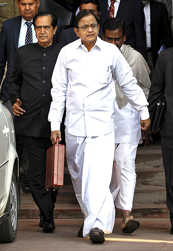 Finance Minister Palaniappan Chidambaram (C) arrives at the parliament to present the 2013/14 federal budget in New Delhi.