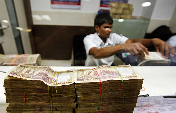 A teller counts currency notes at a bank in Mumbai.