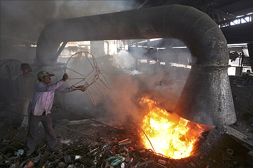 A worker throws a broken iron chair into a furnace for recycling at an iron and steel factory on the outskirts of Jammu.