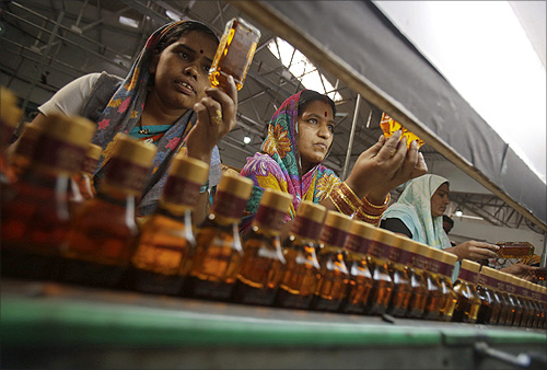 Bottling plant workers check bottles of Black Power whisky for impurities at a Tilaknagar Industries distillery and bottling unit in Srirampur.