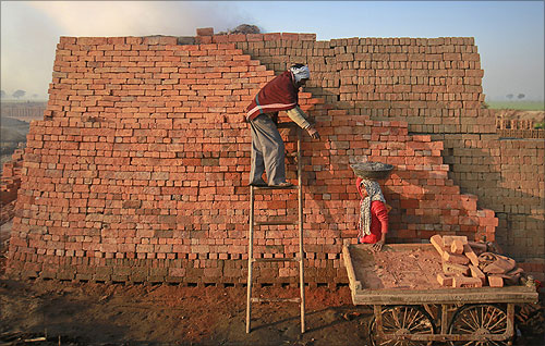 Neeta, 11, helps her father as she carries material to be used for burning fire in a kiln at a brickyard on the outskirts of Kota.