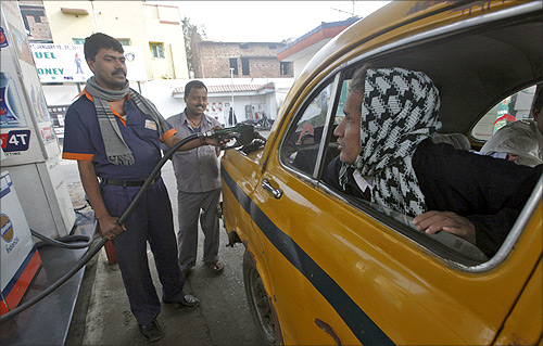 A worker fills diesel in a taxi at a fuel station in Kolkata.