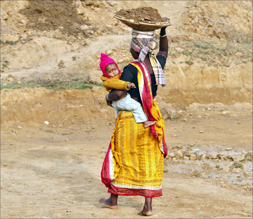 A village woman holds her child while carrying clay on her head as she works at a road construction site under National Rural Employment Guarantee Act.