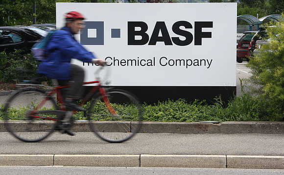 A cyclist rides his bike past the entrance of the BASF plant in Schweizerhalle near Basel, Switzerland.