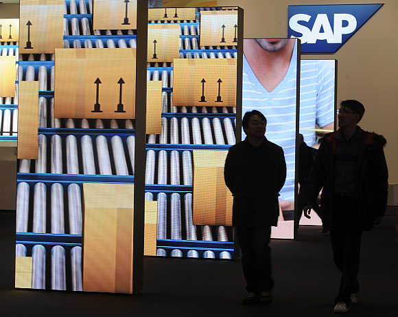 People are pictured beside screens at the booth of German company SAP in Hanover, Germany.
