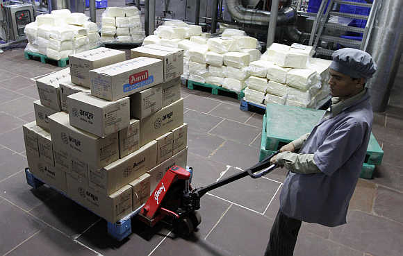 A worker moves a trolley loaded with packed processed cheese in Khatraj village.