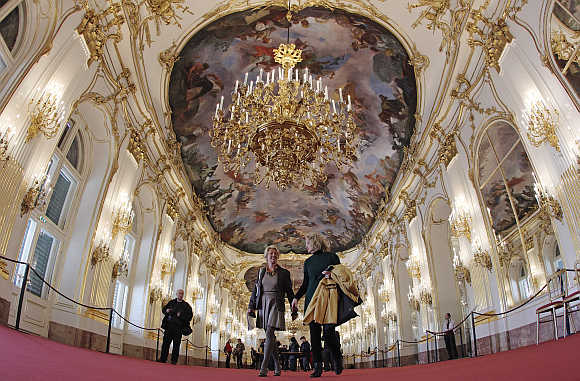 Visitors walk through the Great Gallery hall inside the imperial Schoenbrunn palace in Vienna, Austria.