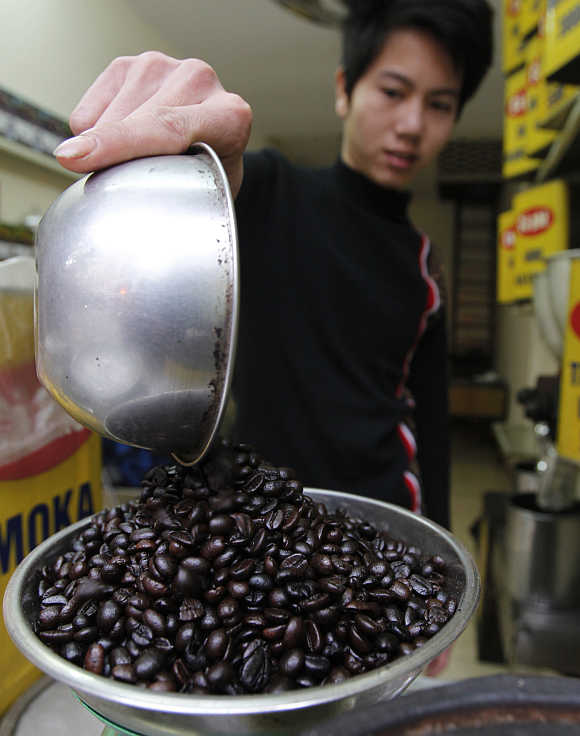 A man weighs coffee beans at Duy Dung coffee shop in Hanoi, Vietnam.