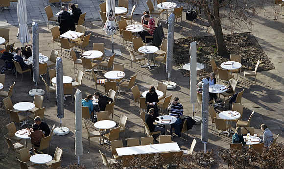 People sit in a coffee garden in Killesberg park in Stuttgart, Germany.