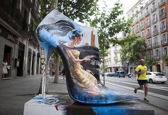 A man jogs past a giant shoe figure, which is part of an exhibition entitled Shoe Street Art, in Madrid.