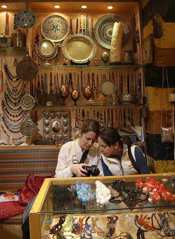 Western tourists visit a handicrafts shop in Old Damascus.