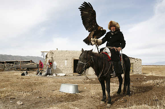 Elik Hamchvay poses with his hunting eagle Khana near Sagsay village in Altay montains in western Mongolia's Bayan Olgiy Province.