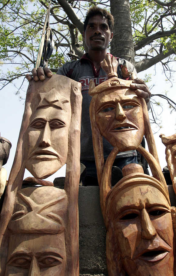 A man selling his carvings for $20 each waits for customers in Dili, East Timor.