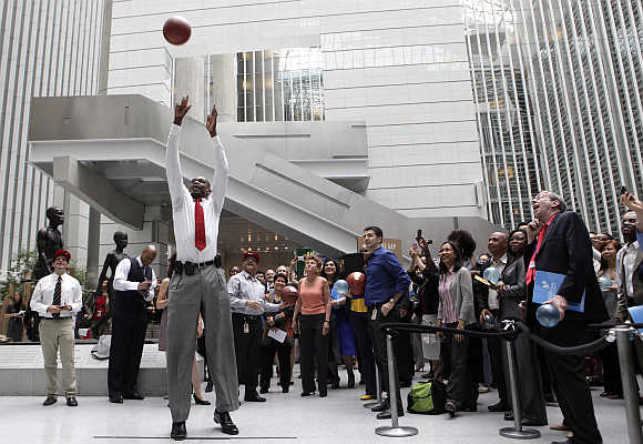 Former National Basketball Association All-Star and current NBA global ambassador Dikembe Mutombo shoots a basket in Washington.