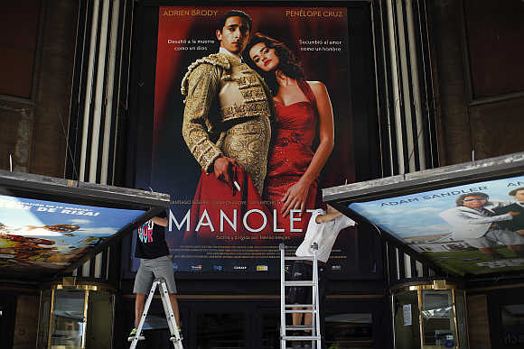 Workers prepare billboards at a cinema in downtown Madrid, Spain.