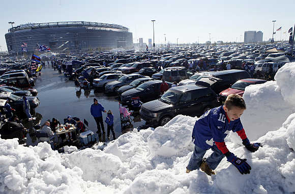 Decklan Corcoran climbs on a pile of snow at MetLife Stadium before the NFL football game between the New York Giants and the Miami Dolphins in East Rutherford, New Jersey.