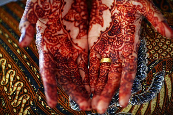 Winda Wahyuni shows her decorated hands and an engagement ring in Banda Aceh, Indonesia.