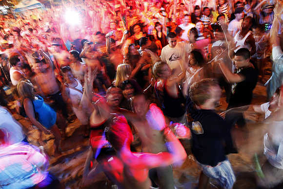 Tourists dance to electronic music during an open-air party at Patong Beach in Phuket.