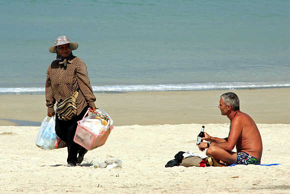 A tourist drinks beer at Patong Beach in Phuket.