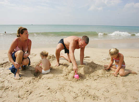 Peter Krantz from Sweden relaxes with his family on Kamala Beach in Phuket.