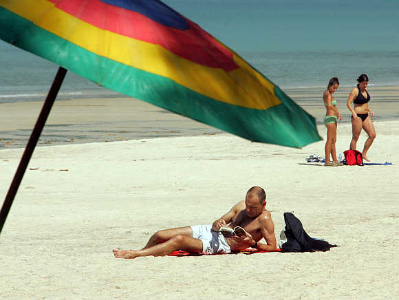 Beachgoers relax at Patong Beach in Phuket.