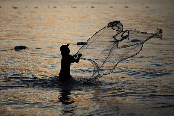 A fisherman casts his net at Patong Beach in Phuket.