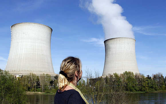 A woman looks at cooling towers of France's Electricite de France nuclear power station in Saint Laurent, Central France.