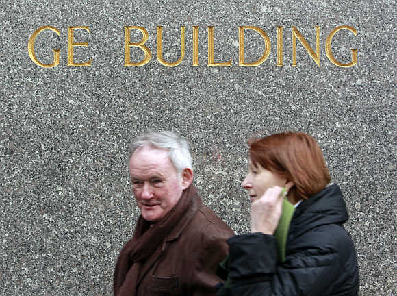 People walk past the General Electric building,