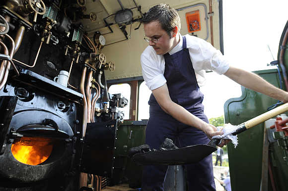 Driver of Tornado 60163 steam train stokes the engine before it moves for the first time at the Darlington Locomotive Works in Darlington, northern England.