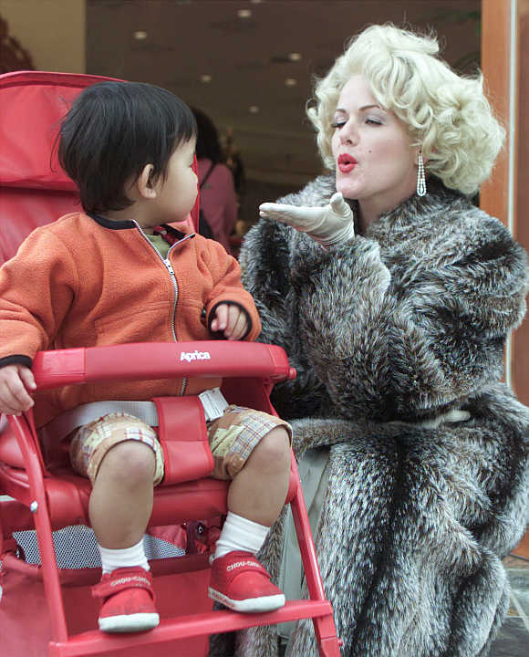 A Marylin Monroe lookalike blows a kiss to a boy in a baby buggy in Osaka, Japan.