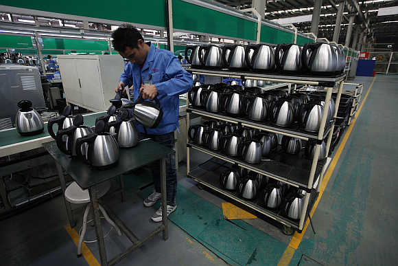 An employee tests electric kettles in Zhongshan, southern Chinese province of Guangdong.