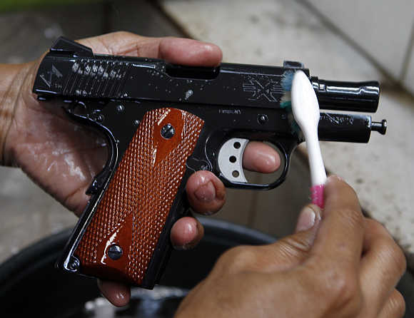 A gun factory worker uses a toothbrush to clean a caliber 45 pistol at Shooters Arms in Cebu city, Philippines.
