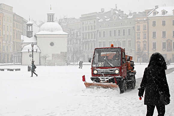 A woman walks as a snow-plough plows snow from the main market square after heavy snowfall in Krakow.